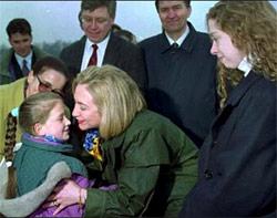 Hillary Clinton on the tarmac in Bosnia. She is speaking to an adorable 8-year-old girl while Chelsea Clinton stands nearby. A crowd stands around; there is no sign of anyone reacting to sniper fire.